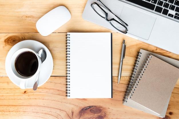 Página do caderno em branco está no topo da mesa de mesa de escritório de madeira com suprimentos em lay plana.