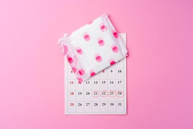 Página do calendário e almofada higiênica feminina na vista superior do fundo rosa