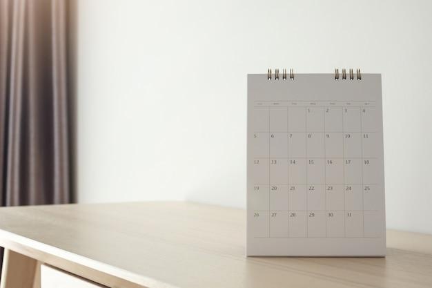 Página do calendário fechada na mesa de madeira na parede branca