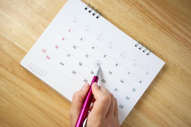 Página do calendário na mesa com uma mão feminina segurando a vista superior da caneta