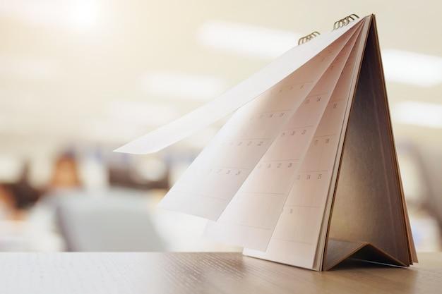 Página do calendário virando folha na mesa de madeira com cronograma de negócios desfocado no interior do escritório