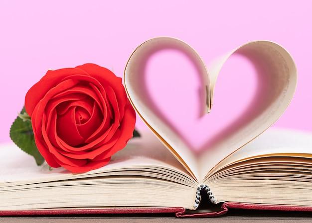 Página do livro curvado forma de coração e rosa vermelha