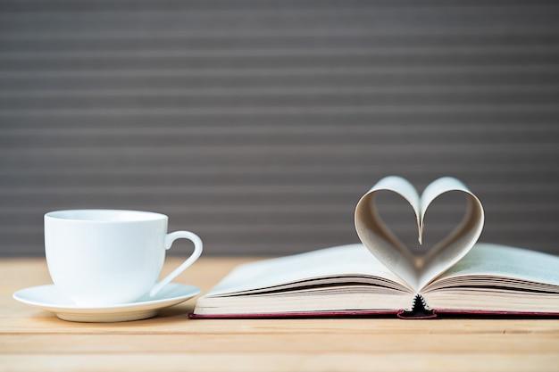 Página do livro forma de coração curvo e xícara de café