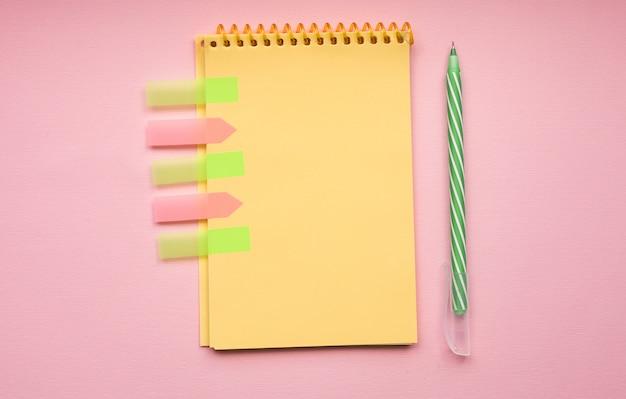 Página em branco de bloco de notas espiral vertical com caneta em rosa