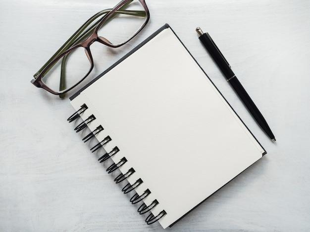 Página em branco do bloco de notas, caneta e óculos