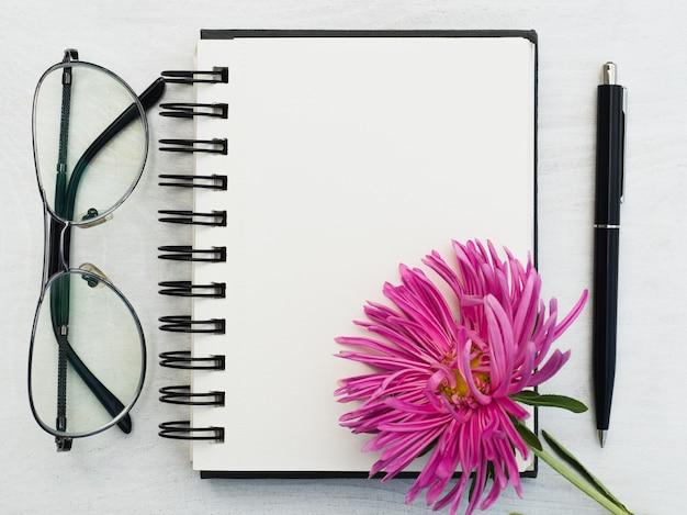 Página em branco do bloco de notas e uma bela flor. close-up, vista de cima, superfície de madeira. conceito de preparação para férias profissionais. parabéns para parentes, amigos e colegas