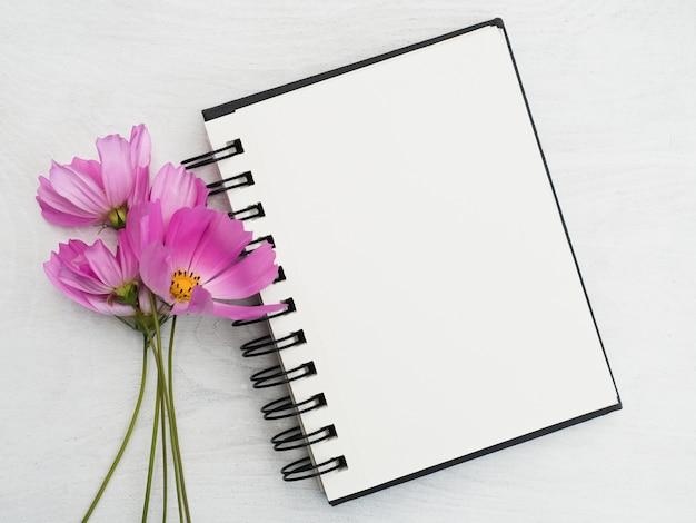 Página em branco do bloco de notas e uma linda flor