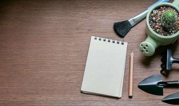 Página em branco do bloco de notas, lápis, cápsula de cacto e mini conjunto de ferramentas de jardim na mesa de madeira.