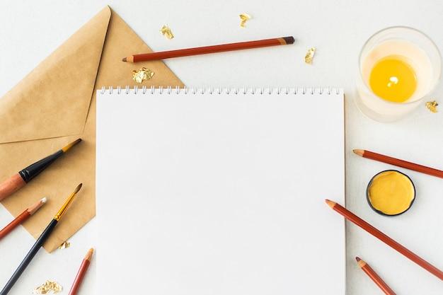 Página em branco do caderno aberto e itens de decoração em cinza