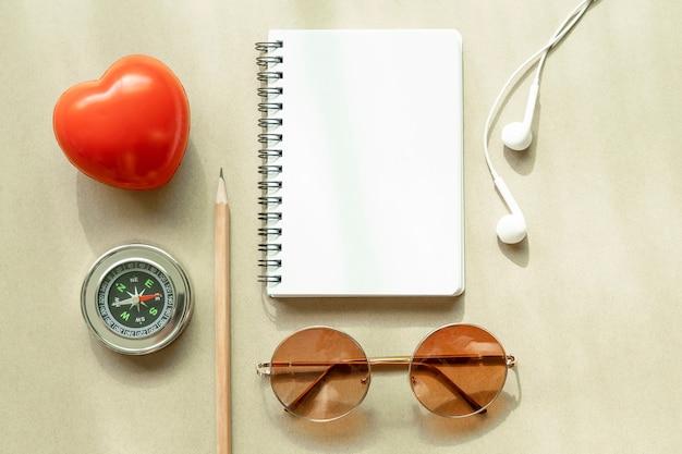 Página em branco do caderno branco aberto com bússola, fone de ouvido, óculos de sol, lápis e coração vermelho na mesa