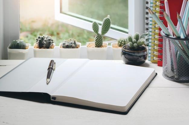 Página em branco do caderno e caneta na mesa de madeira perto da janela aberta com cacto pequeno.