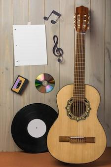 Página musical em branco; cassete; disco compacto; e nota musical preso na parede de madeira com guitarra e disco de vinil