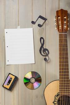 Página musical em branco; fita cassete; disco compacto; e nota musical preso na parede de madeira com guitarra