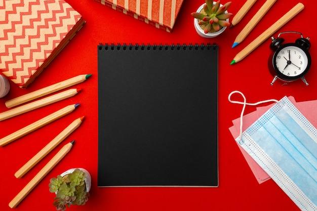 Página preta do bloco de notas com papelaria e máscara médica em fundo vermelho