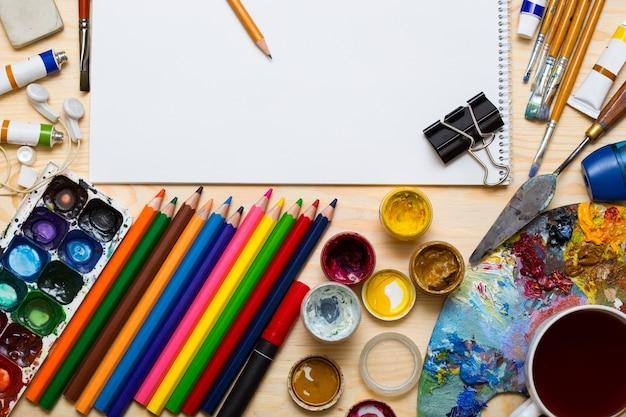 Páginas de álbum e tintas, lápis, óleo, pincel em um fundo de madeira
