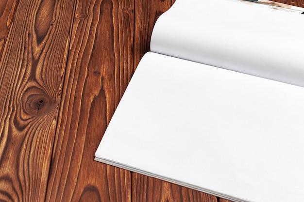 Páginas do diário em branco aberto para o seu espaço de cópia de projeto sobre fundo de madeira