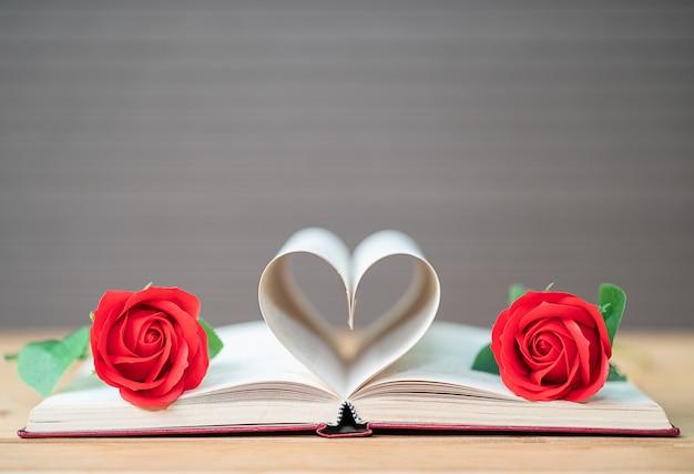 Páginas do livro curvo forma de coração e rosa vermelha