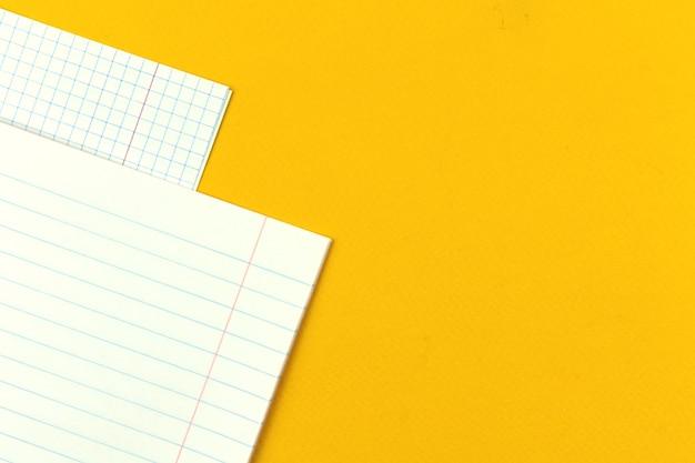 Páginas em branco de um close-up de caderno escolar em um fundo de área de trabalho de mesa amarela com foto do espaço de cópia