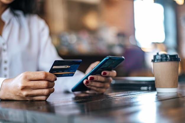 Pague as mercadorias com cartão de crédito através de um smartphone em uma cafeteria.