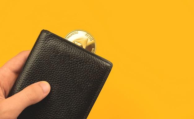 Pague com fundo de conceito ethereum, homem segura carteira de couro preto com moeda de criptomoeda, foto do conceito financeiro e de negócios