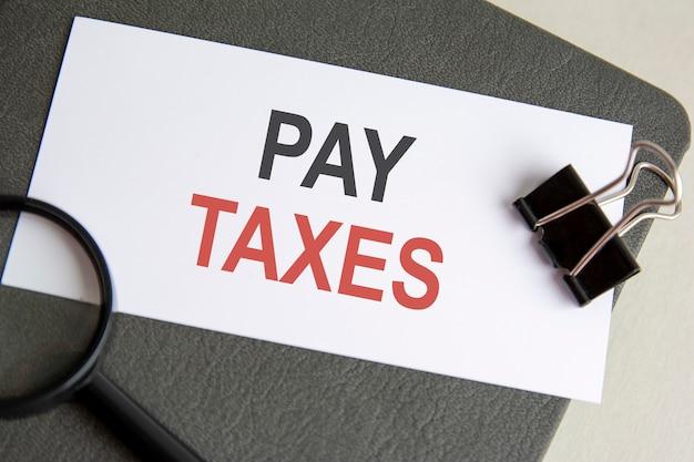 Pague texto de impostos escrito em caderno com clipe para papéis e lupa, plano de fundo cinza
