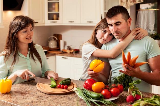 Pai abraçado pela filha na cozinha enquanto prepara comida