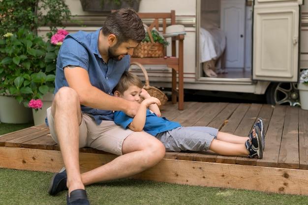 Pai abraçando seu filho ao lado de sua caravana