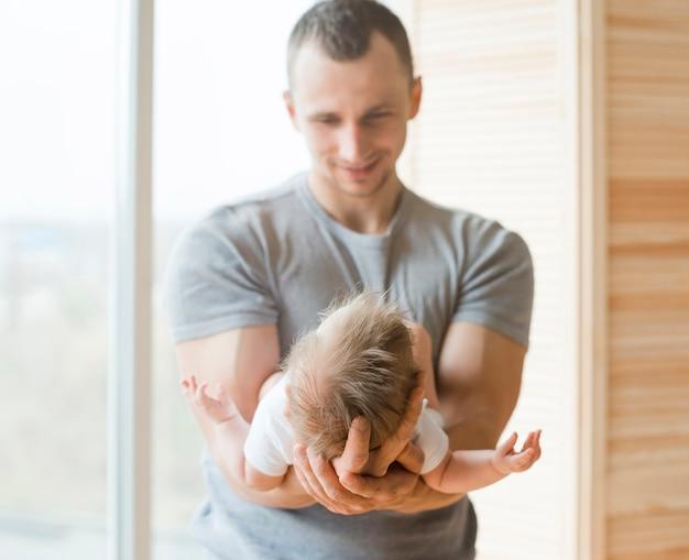 Pai adulto segurando o bebê nas mãos