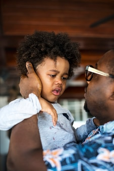 Pai africano acalmando uma criança chorando
