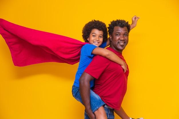 Pai africano e filho jogando super-herói na hora do dia. pessoas se divertindo fundo amarelo. conceito de família amigável.