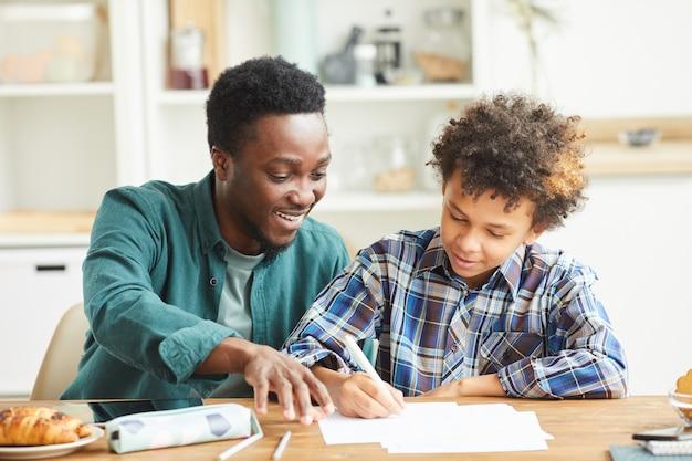 Pai africano sorridente ajudando o filho fazendo a lição de casa, eles sentados à mesa na sala