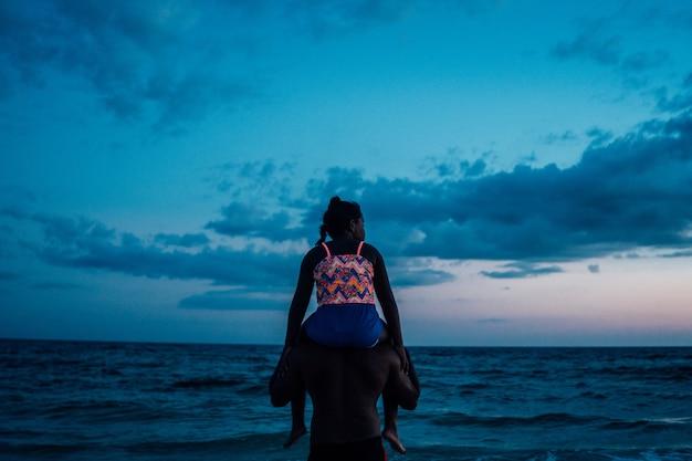 Pai afro-americano com a filha pegando carona nele na praia