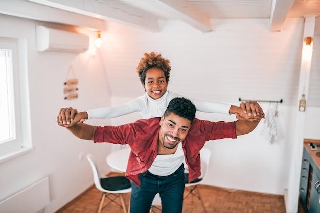 Pai afro-americano e filha que têm o divertimento em casa.
