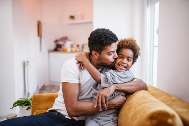 Pai afro-americano feliz e filha pequena bonito em casa. abraçando e beijando.
