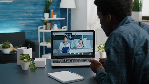 Pai afro-americano na videochamada na internet usando o laptop, falando com o médico da ala do hospital sobre ...