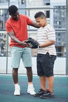 Pai afro-americano positivo com camiseta vermelha mostrando como pegar a bola enquanto explica as regras do beisebol para o filho