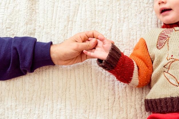 Pai agita as mãos com sua filha bebê deitado na cama.