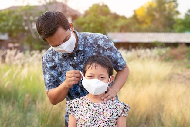 Pai ajuda a filha a usar máscara médica para proteger 2019 - vírus ncov, covid 19 ou corona.
