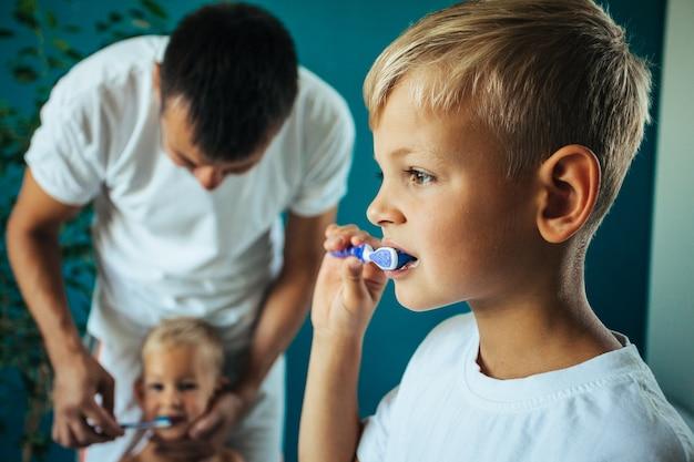 Pai ajuda o garotinho a escovar os dentes