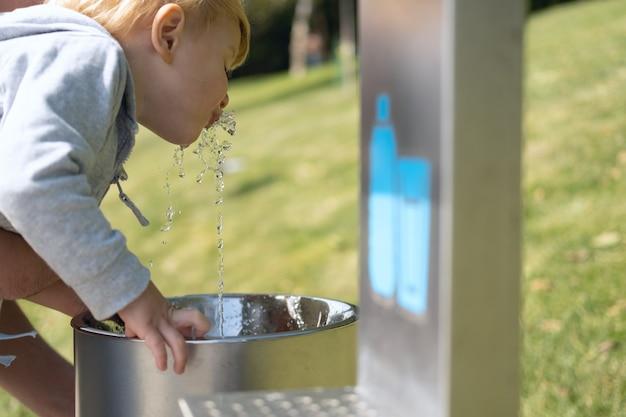 Pai ajuda seu filho a beber água de bebedouro público em um parque