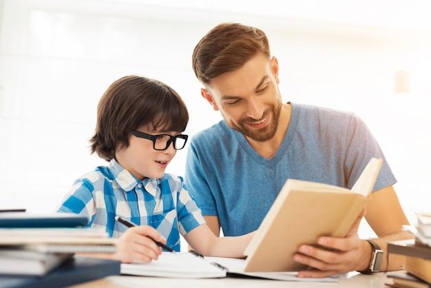 Pai ajuda seu filho a fazer lição de casa na escola.