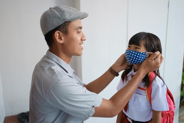 Pai ajudando a filha a usar uma máscara antes de ir para a escola pela manhã para prevenir contra o vírus 19