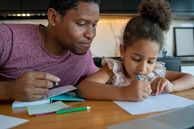 Pai ajudando e apoiando a filha com as aulas em casa enquanto fica em casa
