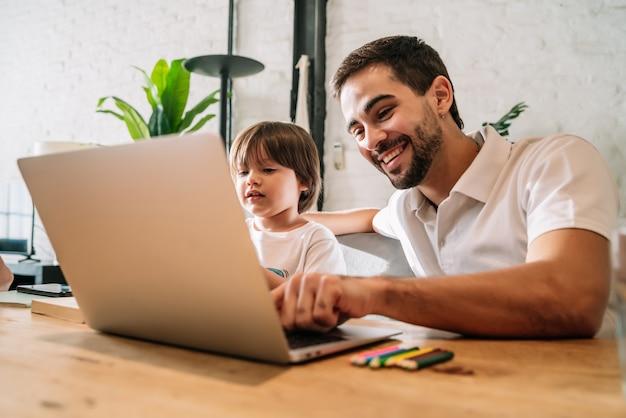 Pai ajudando e apoiando o filho na escola online enquanto fica em casa. novo conceito de estilo de vida normal.