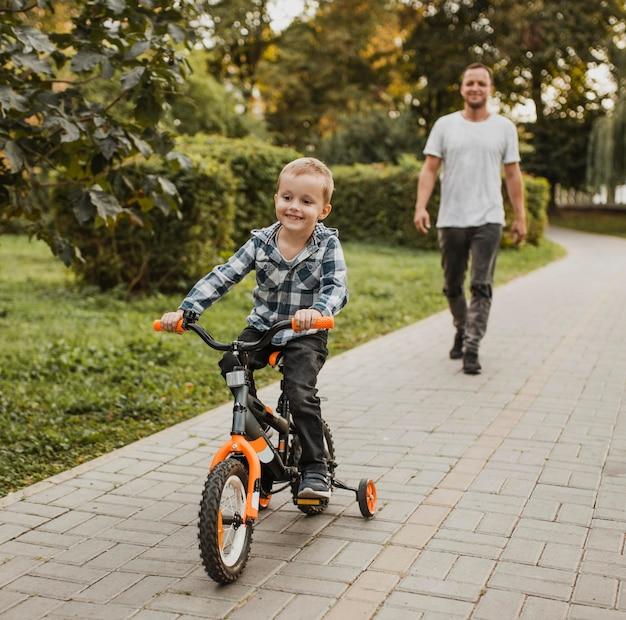 Pai ajudando filho a andar de bicicleta