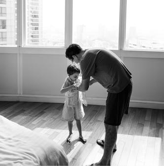 Pai ajudando o filho a se vestir
