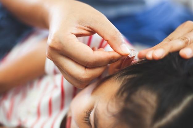 Pai ajudando seu filho a realizar uma lesão no ouvido de primeiros socorros após ter sido um acidente