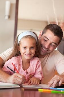 Pai alegre ajudando a filha para o dever de casa