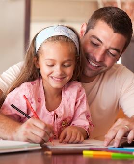 Pai alegre ajudando sua filha a fazer a lição de casa
