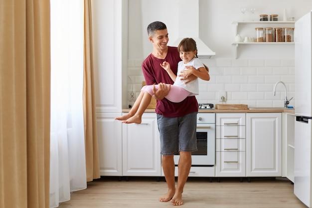 Pai alegre carregando sua filha de cabelos escuros, brincando com a criança pré-escolar feliz dentro de casa contra o conjunto de cozinha, menina criança brincalhona se divertindo com o pai sorridente em casa.